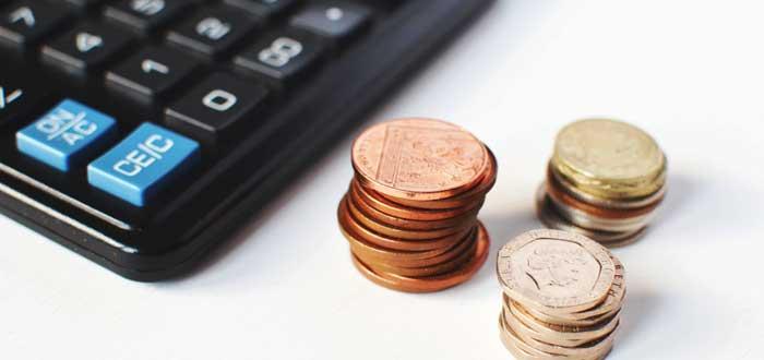calculadora y monedas en fondo blanco-cómo ganan dinero los coworkings-cómo funciona el coworking