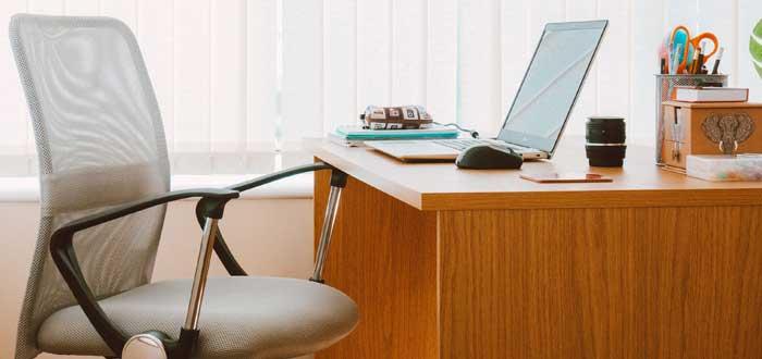 silla ejecutiva y laptop en escritorio dedicado