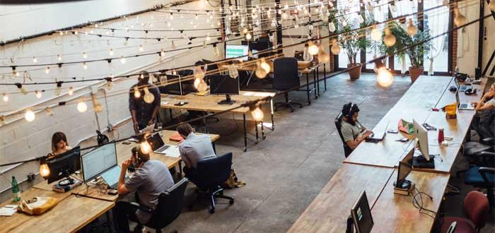 oficina coworking llena de trabajadores autónomos compartiendo espacio de trabajo