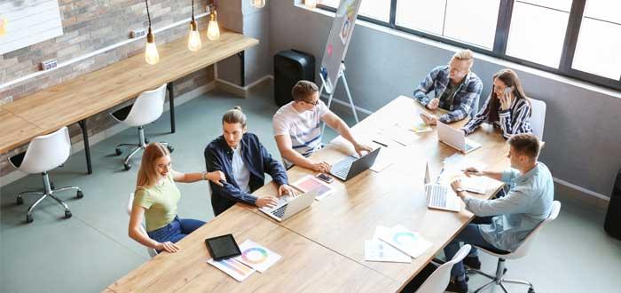 equipo pequeño de coworkers reunidos disicutiendo proyecto