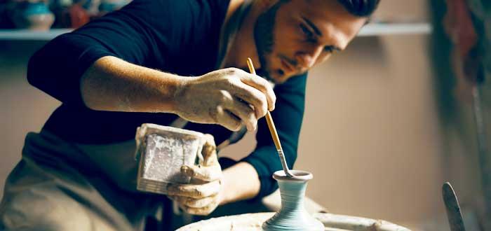 joven trabajando el barro en tipos de coworking para artesanos