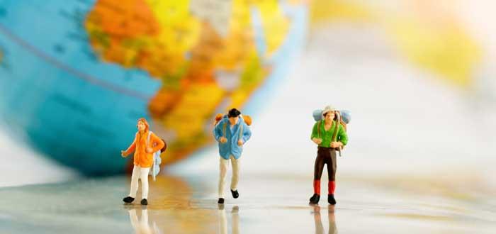miniaturas con mochilas sobre mapa para viajar por el mundo trabajando