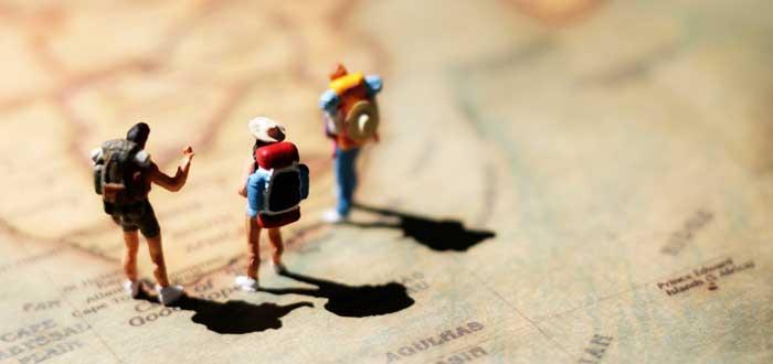miniaturas-con-mochilas-paradas-sobre-mapa-del-mundo-para viajar-mientras-trabajan