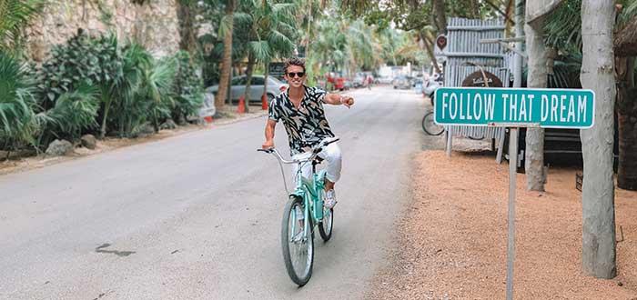 nómada digital subido en bicicleta señalando cartel