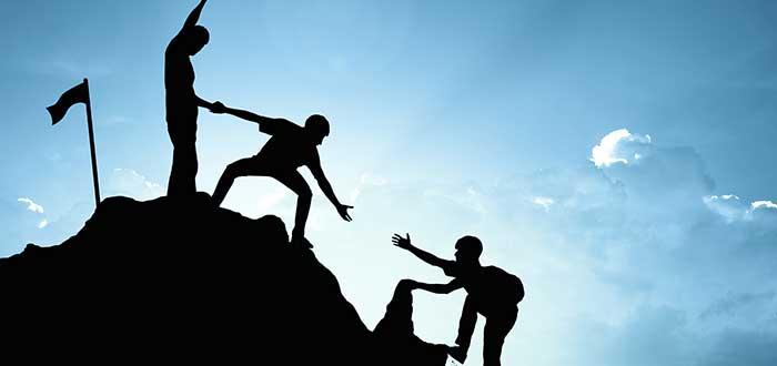 personas ayudando a otra subiendo montana