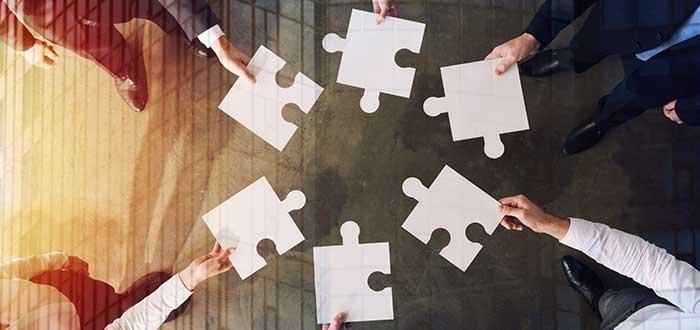 equipo de profesionales uniendo piezas de rompecabezas para disfrutar de los beneficios del trabajo en equipo
