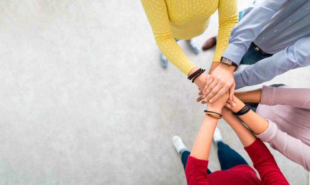 equipo de trabajo poniendo sus manos una encima de la otra