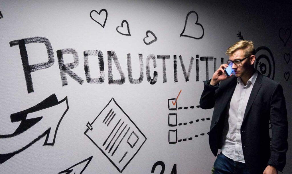 joven hablando por celular con cartel detrás de productividad