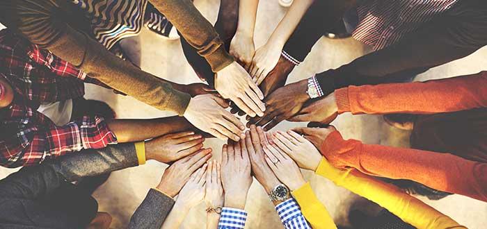 personas-en-equipo-poniendo-sus-manos-al-centro-juntos
