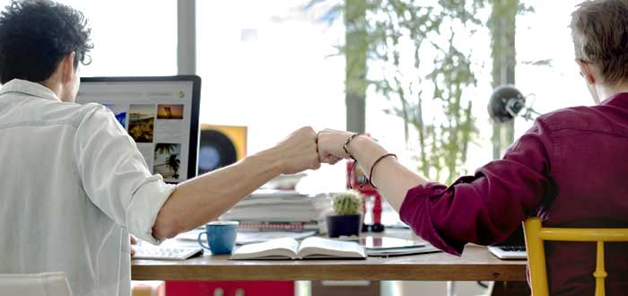 Dos empleados chocando puños a gusto por las ventajas del trabajo en equipo