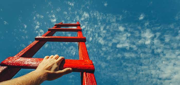 mano-sujetando-escalera-apuntando-hacia-crecimiento