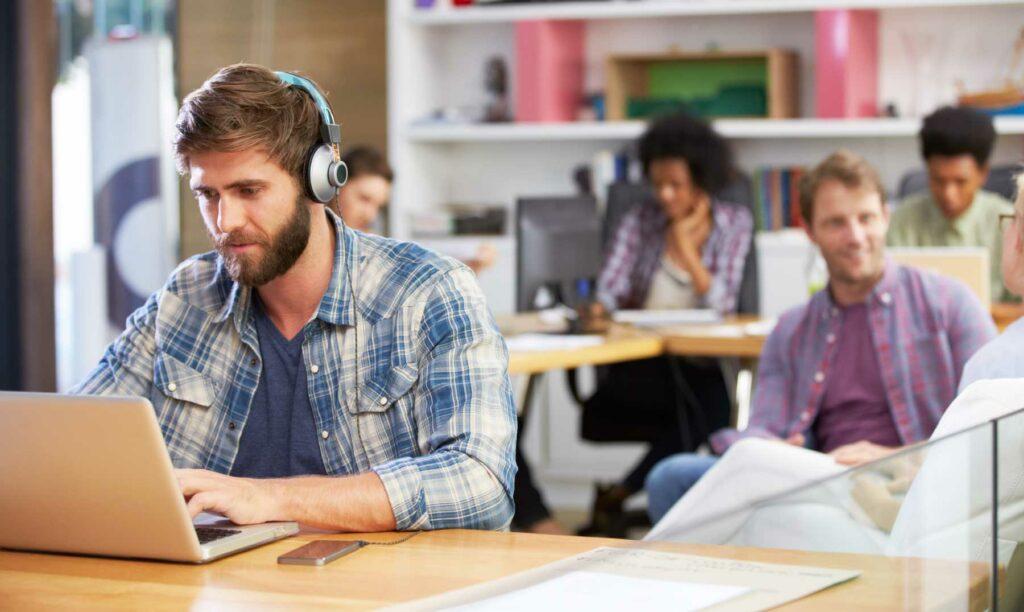 profesional-trabajando-laptop-sentado-hot-desking
