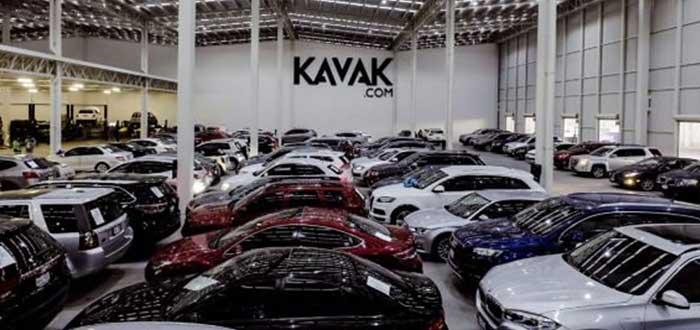 Vehículos aparcados frente a una pared con el logo de Kavak