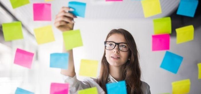 Trabajadora organizando pensamiento visual con post it